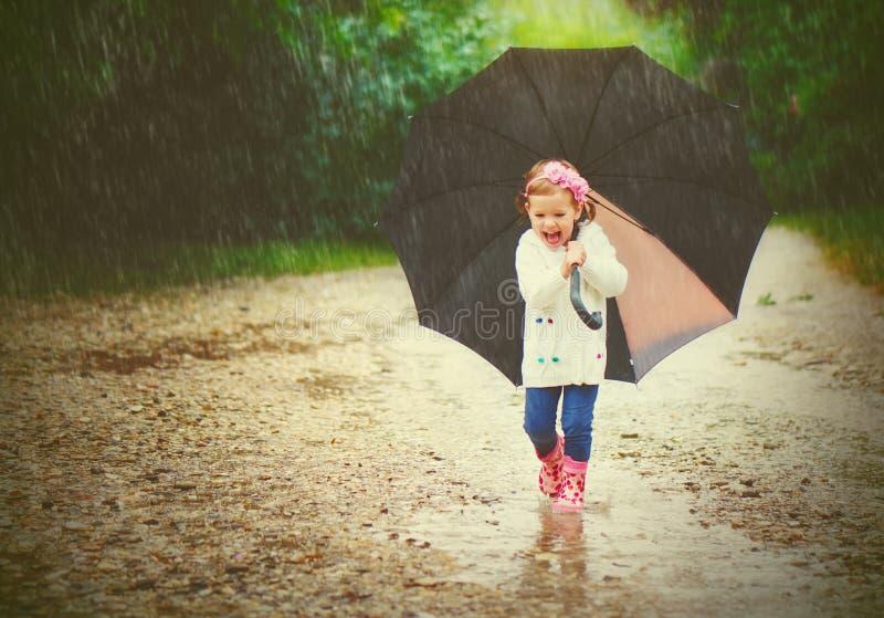 Lyckligt behandla som ett barn flickan med ett paraply i regnkörningarna igenom royaltyfri foto