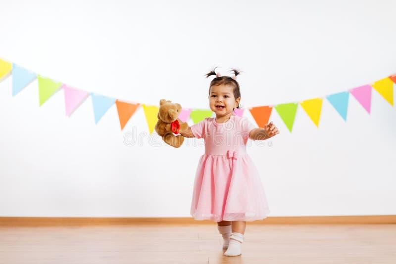 Lyckligt behandla som ett barn flickan med nallebjörnen på födelsedagpartiet arkivbilder