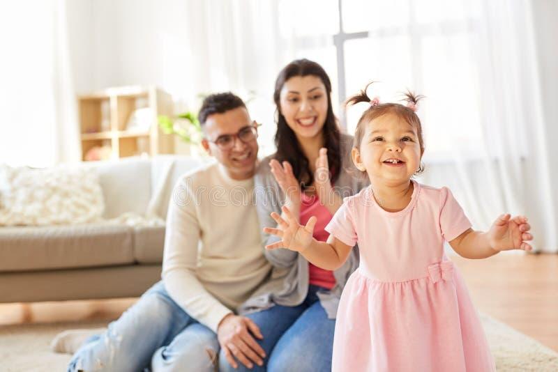 Lyckligt behandla som ett barn flickan och föräldrar hemma arkivfoto