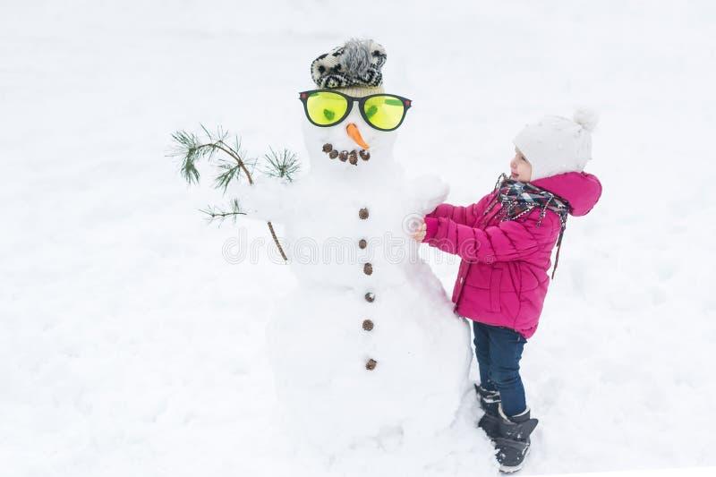 Lyckligt behandla som ett barn flickan som plaing med en snögubbe i exponeringsglas på en snöig vinter, går arkivbilder