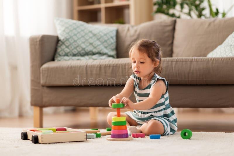 Lyckligt behandla som ett barn flickan som spelar med leksakkvarter hemma fotografering för bildbyråer