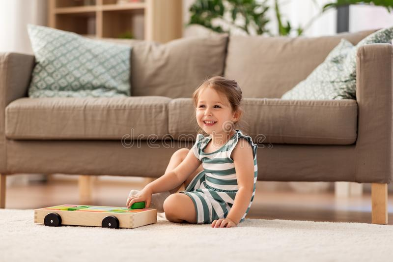 Lyckligt behandla som ett barn flickan som spelar med leksakkvarter hemma royaltyfri foto