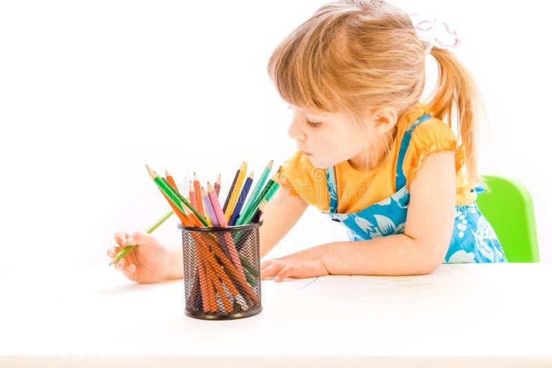 Lyckligt behandla som ett barn härlig målning för flickan på staffli på en vit bakgrund royaltyfri fotografi