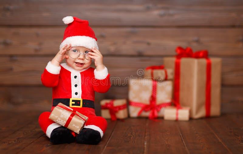 Lyckligt behandla som ett barn i en juldräkt Santa Claus med gåvor royaltyfria foton