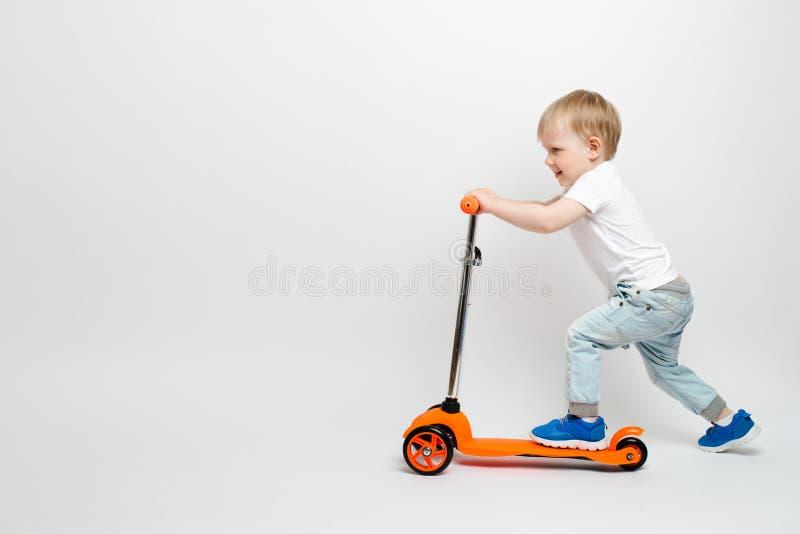 Lyckligt behandla som ett barn lilla barnet i jeans rider en orange sparkcykel på en vit bakgrund i studion royaltyfri foto