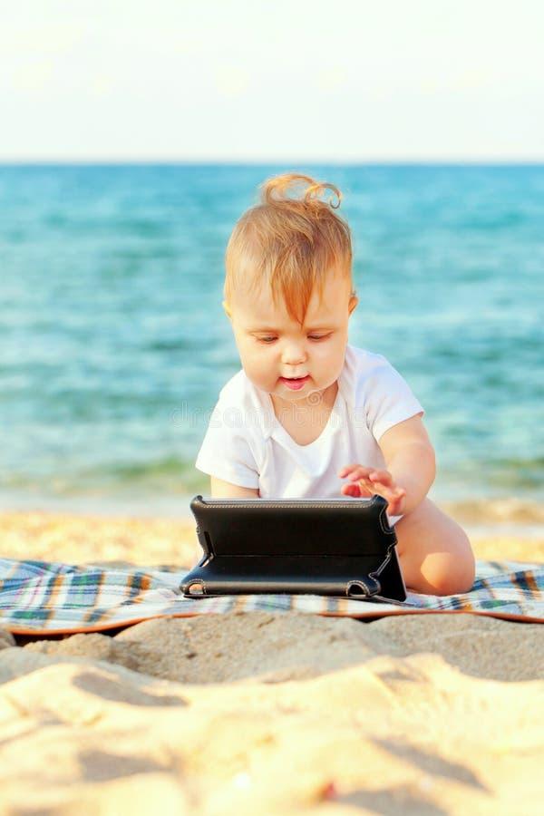 Lyckligt behandla som ett barn med minnestavlaPC på stranden royaltyfria bilder