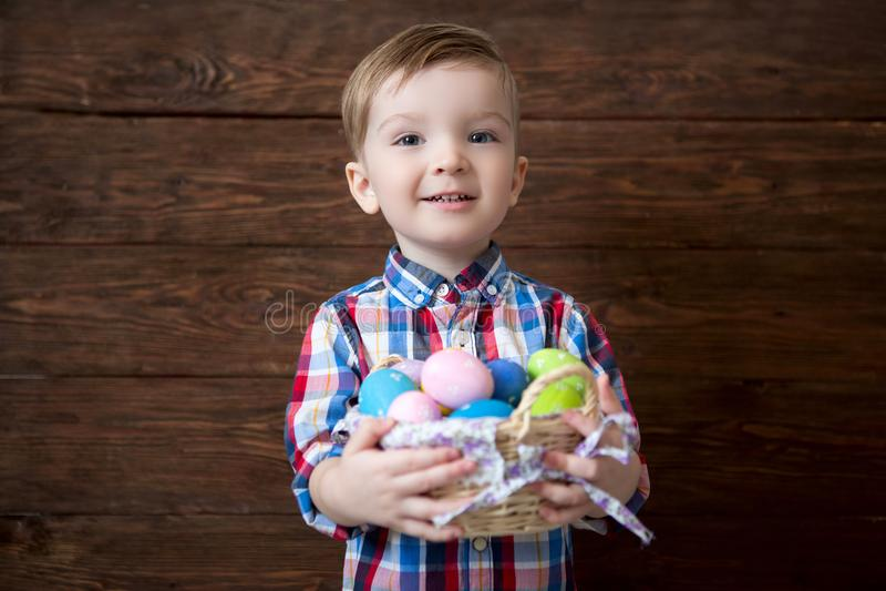 Lyckligt behandla som ett barn pojken med en korg av easter ägg på träbakgrund fotografering för bildbyråer
