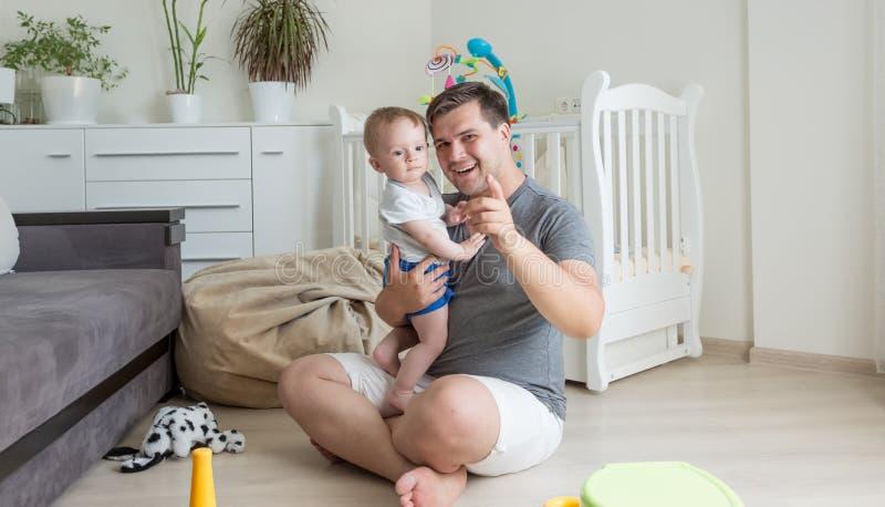 Lyckligt behandla som ett barn pojken och fadern som spelar på golv royaltyfria foton