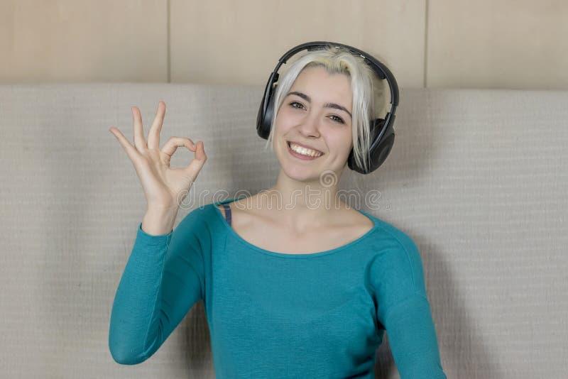 Lyckligt blont sammanträde för ung kvinna på soffan med hörlurarlisteni arkivbild