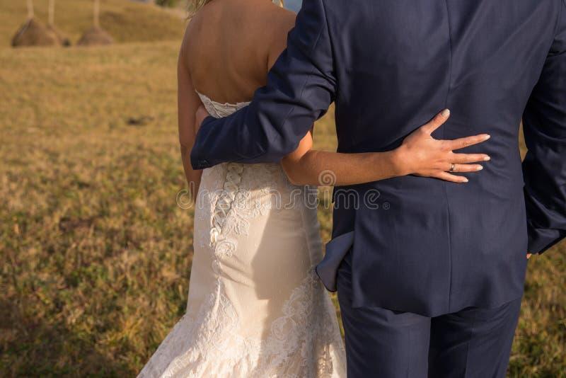 Lyckligt brud- och brudguminnehav runt om de och gå i natur på bröllopdag Gifta sig förälskade par, nygifta personer, fri spac arkivfoto