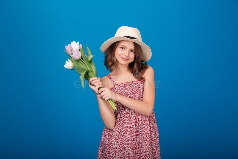 Lyckligt charmigt liten flickaanseende och hållande bukett av tulpan fotografering för bildbyråer