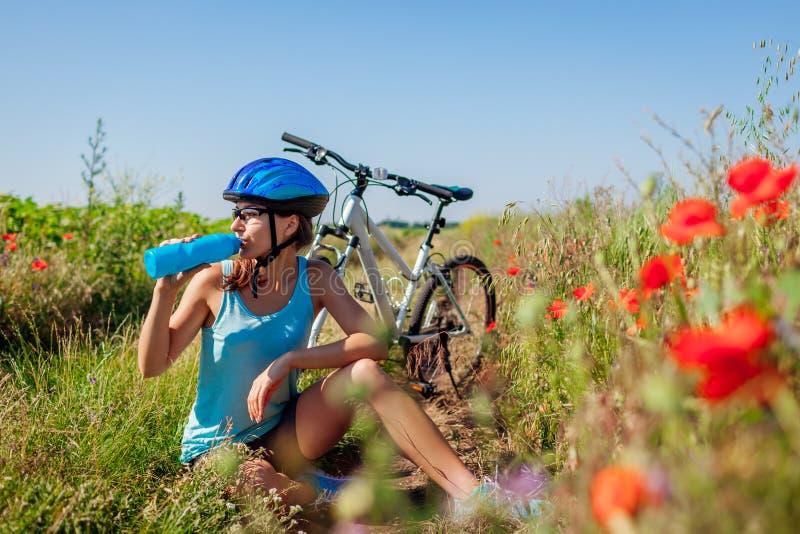 Lyckligt cyklistdricksvatten för den unga kvinnan och att ha vilar, når de har ridit cykeln i sommarfält arkivfoto