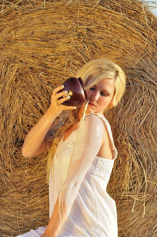 Lyckligt dricka för kvinna mjölkar från cruse eller bilskrället royaltyfri bild