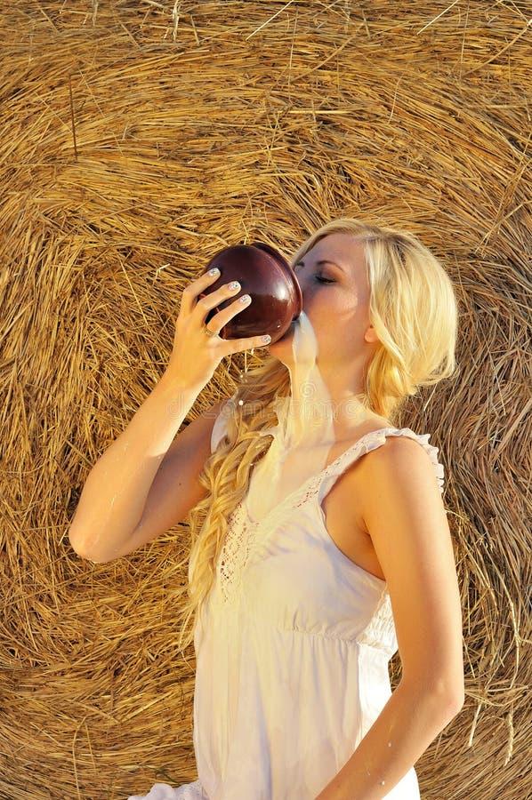 Lyckligt dricka för kvinna mjölkar från cruse eller bilskrället royaltyfri fotografi