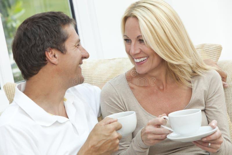 Lyckligt dricka Tea eller kaffe för man- & kvinnapar arkivbilder
