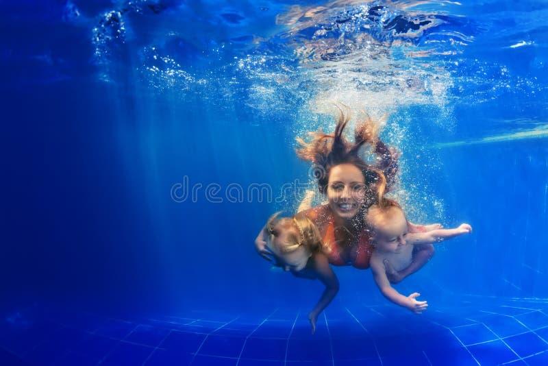 Lyckligt dyka för familj som är undervattens- med gyckel i simbassäng fotografering för bildbyråer