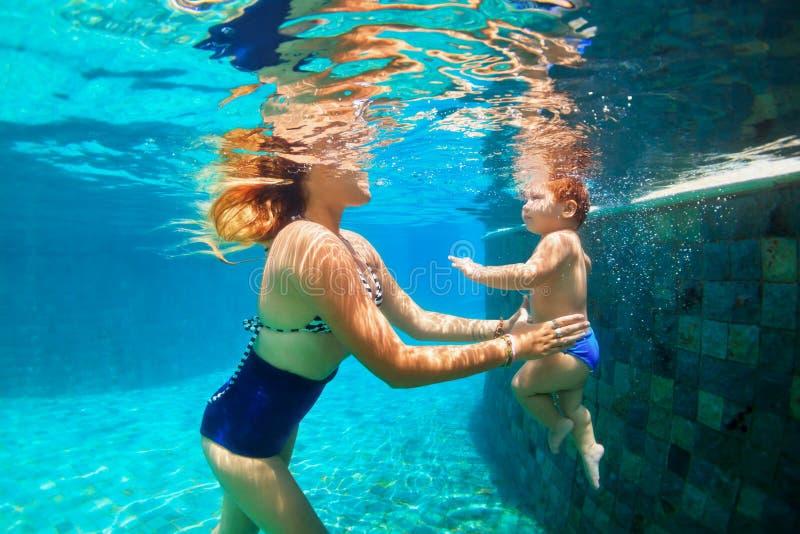 Lyckligt dyka för familj som är undervattens- med gyckel i simbassäng arkivbild