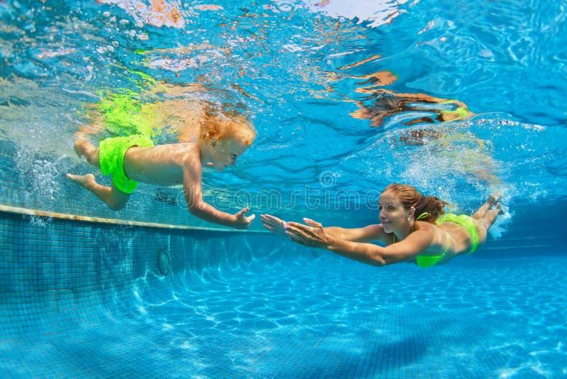 Lyckligt dyka för familj som är undervattens- med gyckel i simbassäng royaltyfria bilder