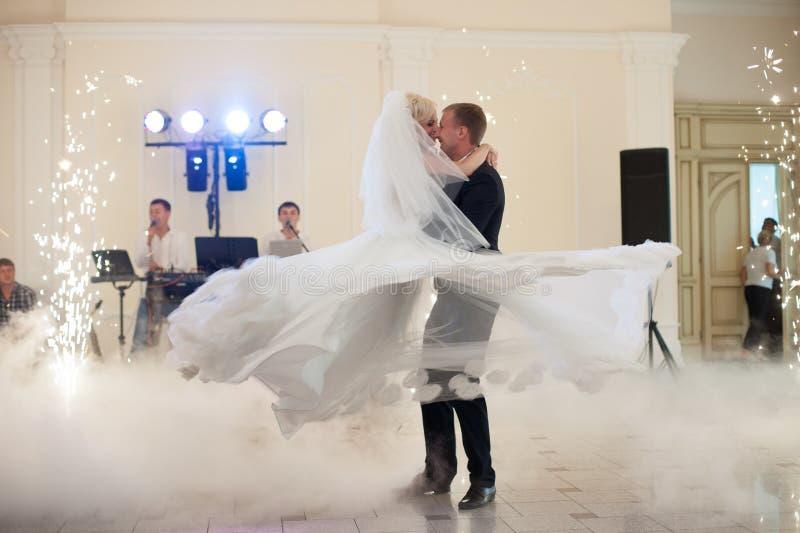 Lyckligt elegant gift par som utför den första dansen i en restaur royaltyfri bild