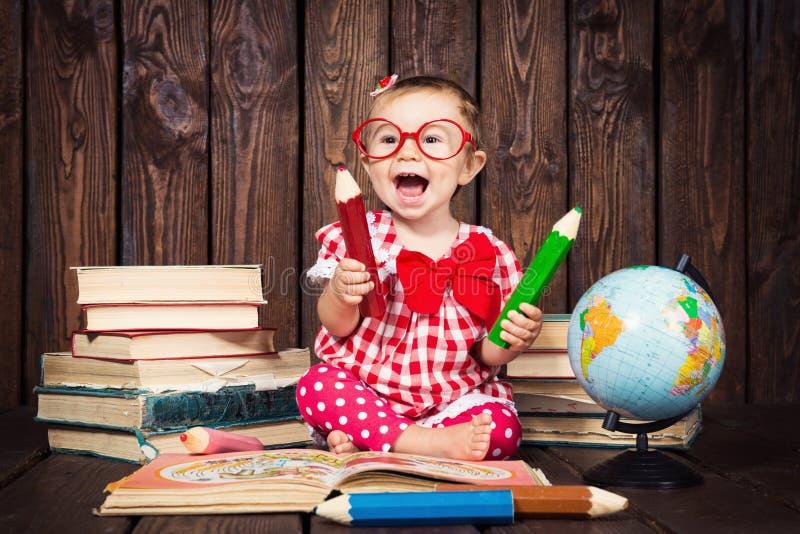 Lyckligt en trevlig liten flicka med exponeringsglas och blyertspennor mot bakgrunden av böcker och ett jordklot royaltyfri fotografi
