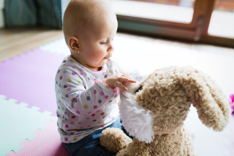 Lyckligt ett årigt flickasammanträde med den flotta leksaken royaltyfri fotografi