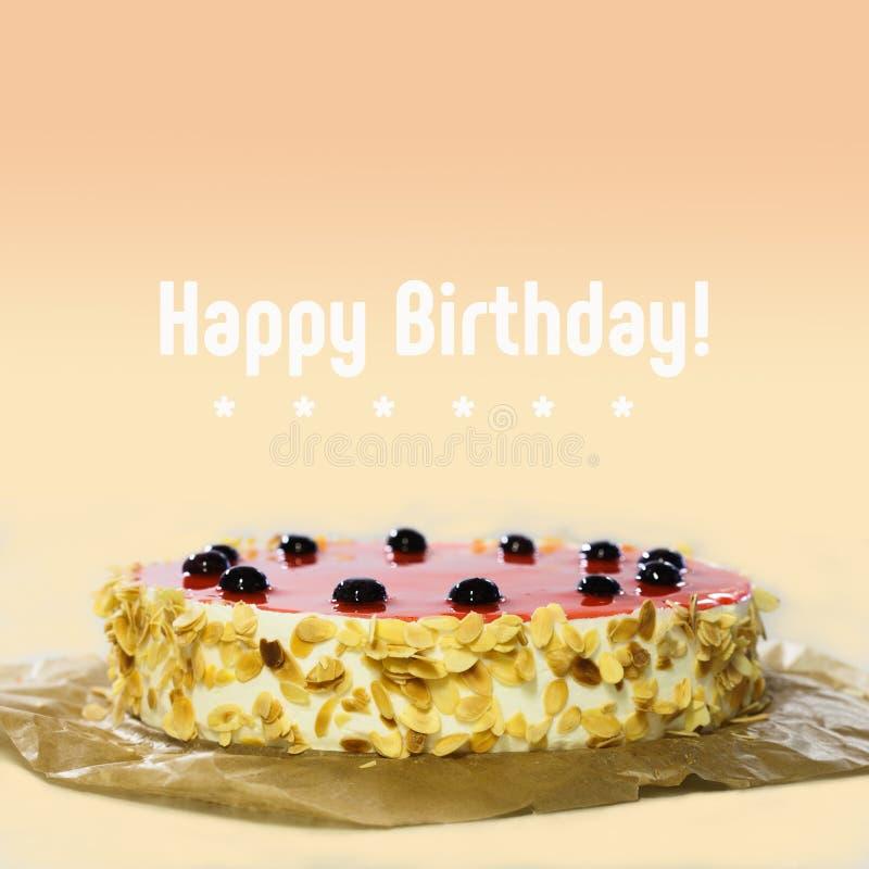 lyckligt födelsedagkort Baka ihop med den svarta körsbäret, röd gelé, mandelflingor Söt efterrätt på bakgrund för persikafärglutn royaltyfri foto