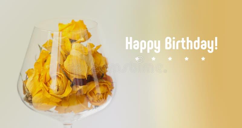 lyckligt födelsedagkort Torkat steg blommor i vinexponeringsglas, beige lutningbakgrund gul kronbladmakrosikt, kopieringsutrymme arkivfoto