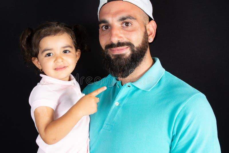Lyckligt förhållande av den stiliga fadern och den gulliga dotteromfamningen tillsammans mot svart bakgrund royaltyfria foton