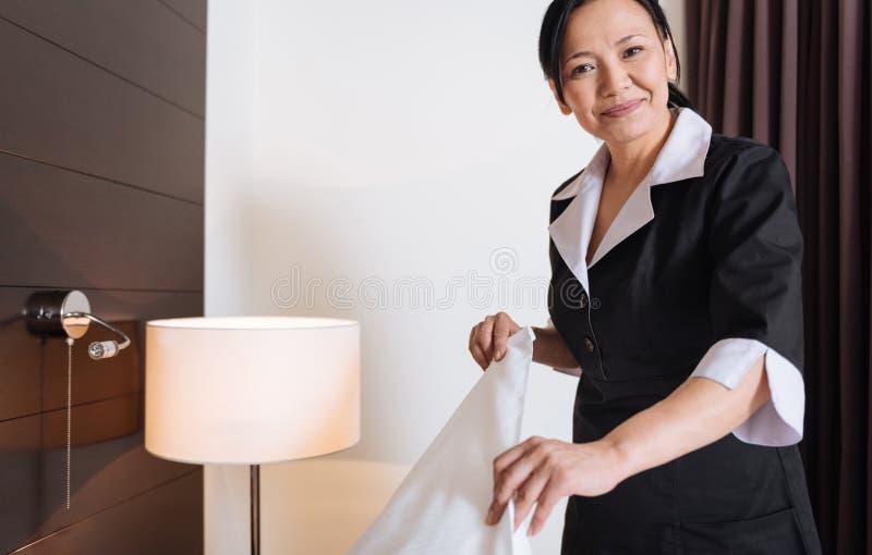 Lyckligt förtjust kvinnaarbete som en hotellhembiträde royaltyfria bilder