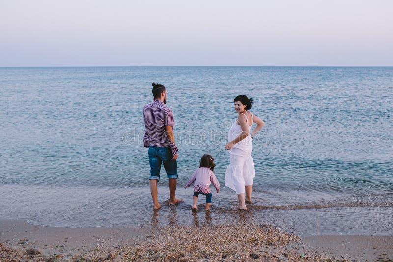 Lyckligt familjanseende på stranden och se havet royaltyfria foton