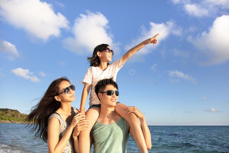 Lyckligt familjanseende på strandklockan solnedgången royaltyfri fotografi