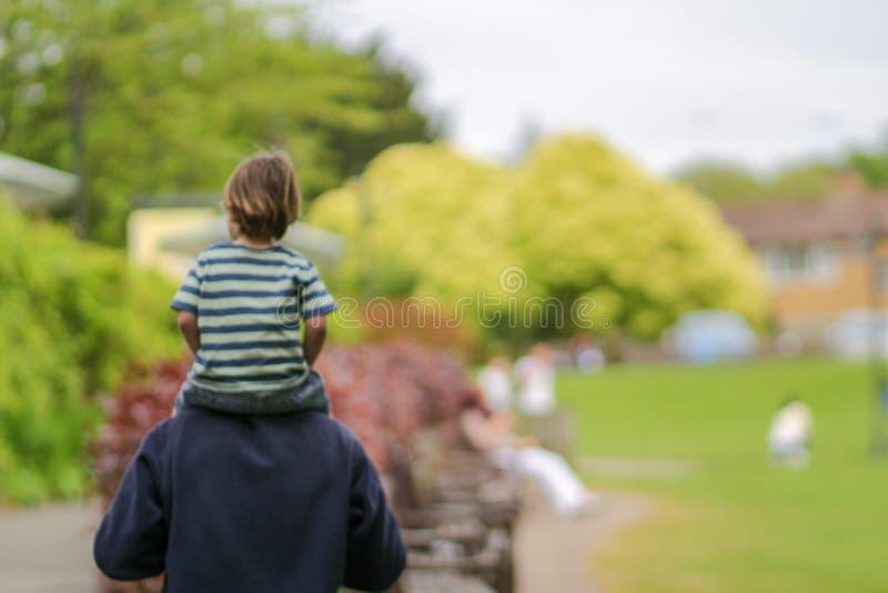 Lyckligt familjbegrepp - den suddiga bilden av barnet, som sitter på faderhals, och att ha gyckel parkerar in på solig dag royaltyfri bild