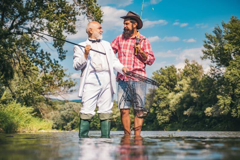 Lyckligt familjbegrepp - fader och son tillsammans Flugasportfiskare på floden Fiska i floden Manfiske Alla ?ldras kategorier - s arkivfoto