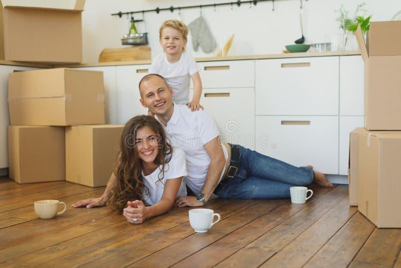 Lyckligt familjflyttninghem med askar omkring royaltyfri fotografi