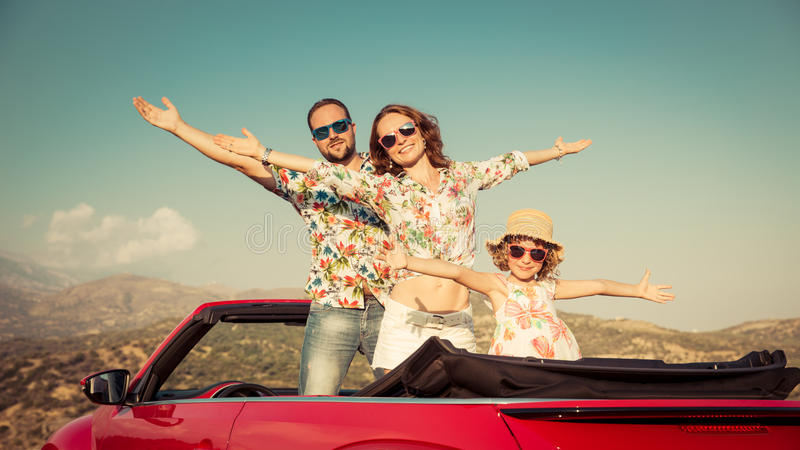 Lyckligt familjlopp med bilen i bergen royaltyfri bild