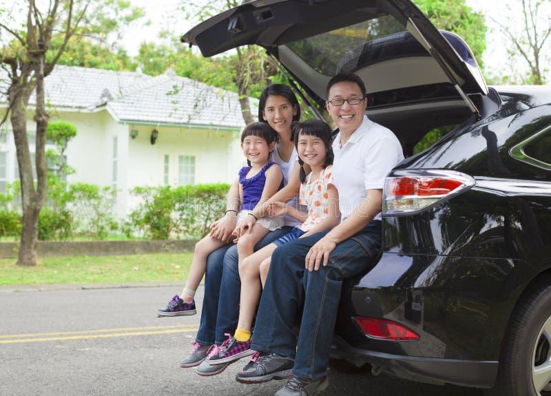 Lyckligt familjsammanträde i bilen och deras hus bakom royaltyfri fotografi
