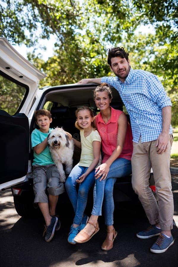 Lyckligt familjsammanträde i bilstam med deras hund arkivbilder