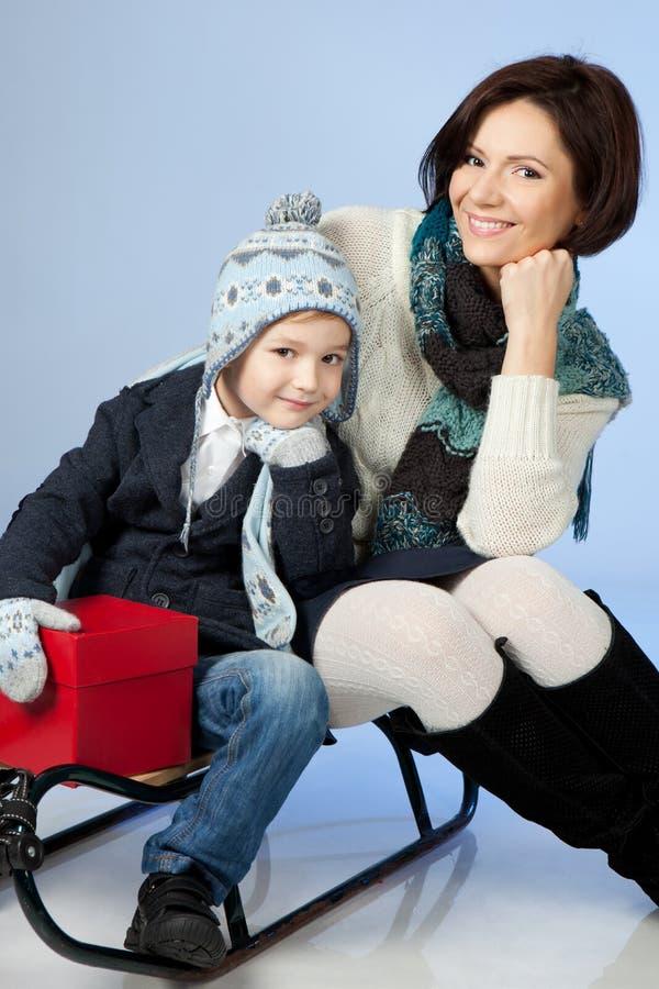 Lyckligt familjsammanträde på en Sled på vintern Time royaltyfria foton