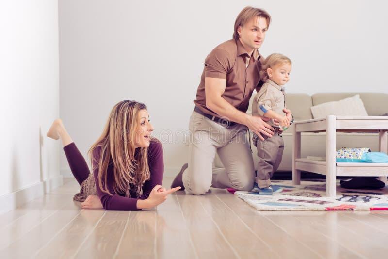 Lyckligt familjsammanträde på golv med deras litet behandla som ett barn Familj som hemma spenderar tid med deras son arkivbild