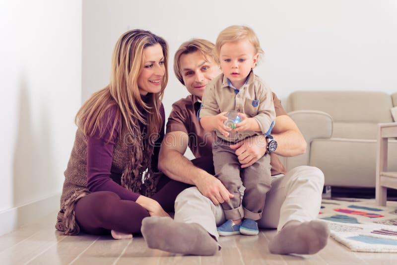 Lyckligt familjsammanträde på golv med deras litet behandla som ett barn Familj som hemma spenderar tid med deras son royaltyfri bild
