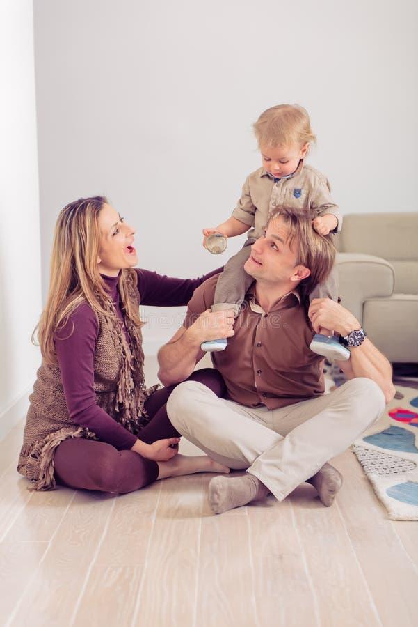 Lyckligt familjsammanträde på golv med deras litet behandla som ett barn Familj som hemma spenderar tid med deras son royaltyfria foton