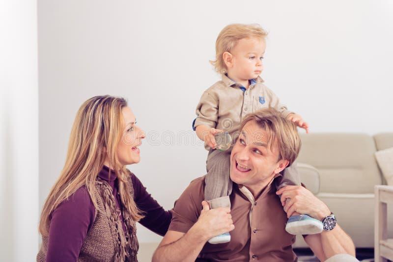 Lyckligt familjsammanträde på golv med deras litet behandla som ett barn Familj som hemma spenderar tid med deras son arkivfoton