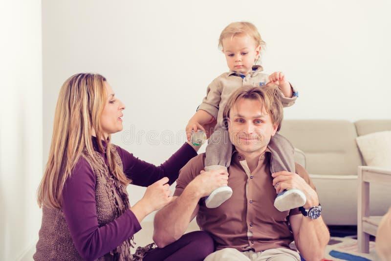 Lyckligt familjsammanträde på golv med deras litet behandla som ett barn Familj som hemma spenderar tid med deras son arkivbilder