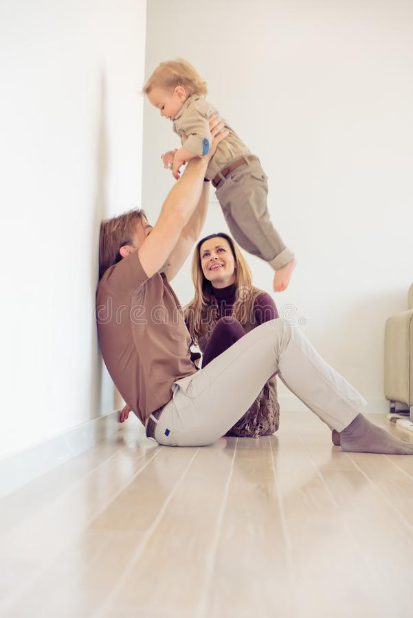 Lyckligt familjsammanträde på golv med deras litet behandla som ett barn Familj som hemma spenderar tid med deras son Fadern lyft royaltyfri foto
