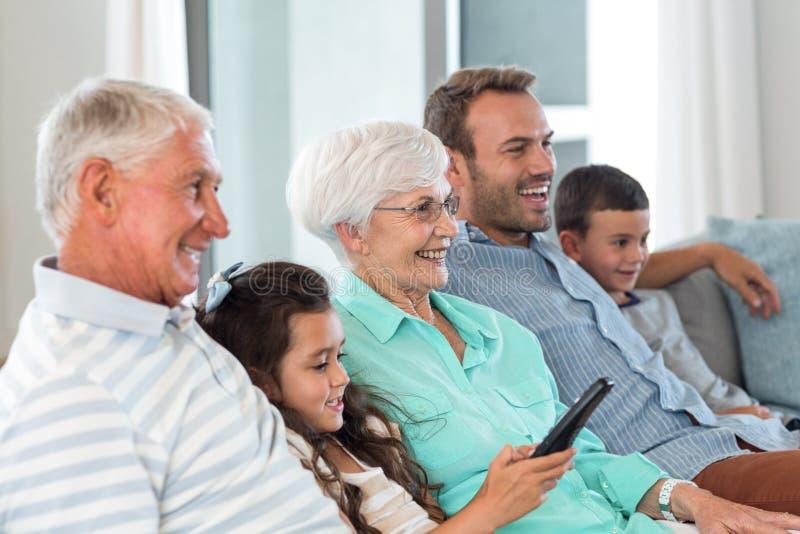Lyckligt familjsammanträde på soffan fotografering för bildbyråer