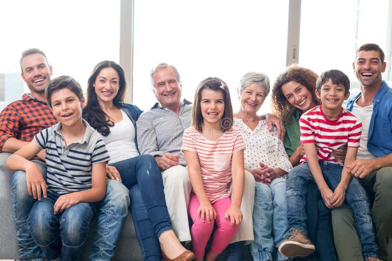 Lyckligt familjsammanträde på soffan royaltyfri fotografi