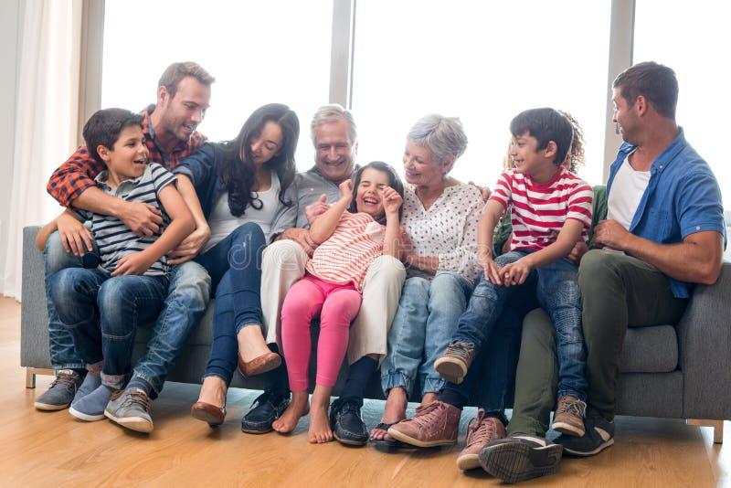 Lyckligt familjsammanträde på soffan royaltyfri bild