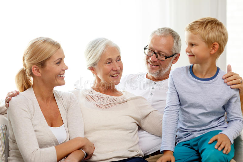 Lyckligt familjsammanträde på soffan hemma arkivfoton