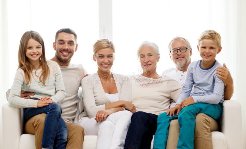 Lyckligt familjsammanträde på soffan hemma royaltyfri foto