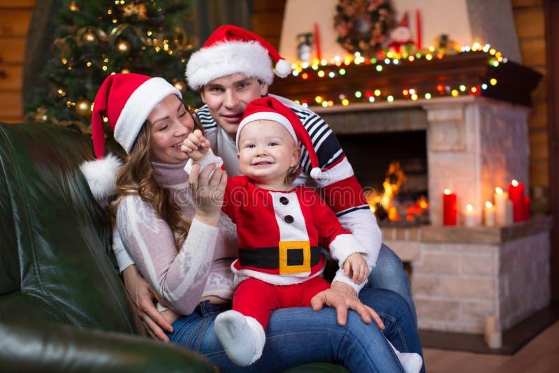 Lyckligt familjsammanträde på soffan nära julgranen och spisen i vardagsrum fotografering för bildbyråer